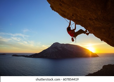 Young man climbing overhanging cliff at sunset, Kalymnos island, Greece. Beautiful evening view of Telendos island in background.