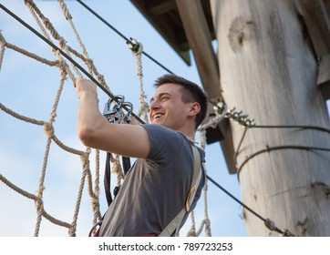 young man at climbing park or high rope garden