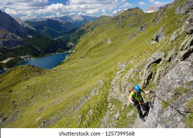 Young man climbing via ferrata delle Trincee near Arabba in the Dolomites (Dolomiti mountains in Italy), with Lake Fedaia in background, on a sunny day of summer