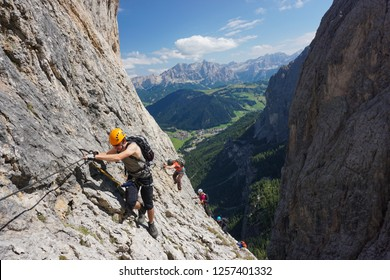Young man climbing via ferrata Brigata Tridentina in the Dolomites (Dolomiti mountains in Italy) on a sunny day of summer