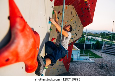Young man climbing wall rock an extreme sport