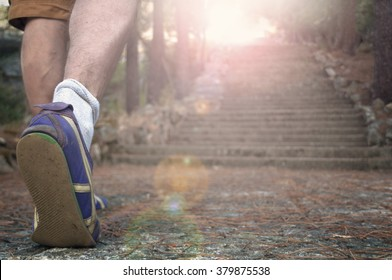 Young man climbs the stairs of the forest with a bright back-light