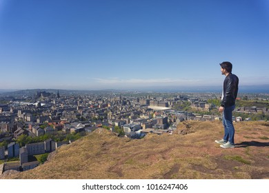 Young man close to the edge of Salisbury Crags, Arthur Seat, Edinburgh, Scotland. Taken during spring time.