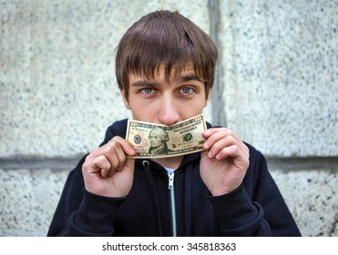 Young Man close the Mouth with American Dollars by the Wall