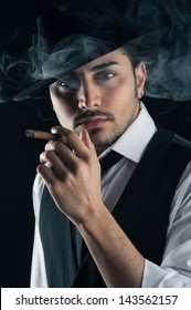 Young man close up portrait with cigar against dark background.