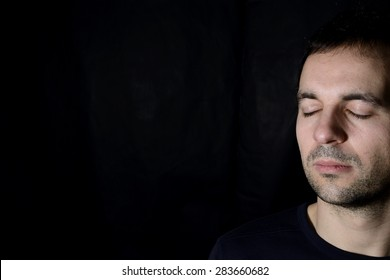 young man with closed eyes, black background