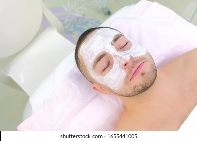 Young man with closed eyes and white mak on face lying on couch in beauty clinic, spa procedure. Relaxing, waiting time, face closeup, top view. Beauty industry concept. Guy enjoying in cosmetology.