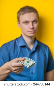 A young man close-up in a blue shirt on a yellow background, gives or takes money. Dollars. Holds money in hands. . Photos