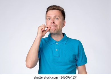 Young man closing mouth and lips shut as zip with fingers. Secret and silent, taboo talking concept