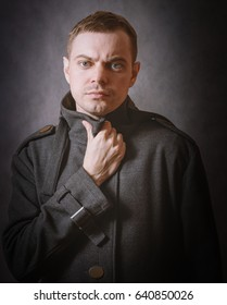 Young man in coat on dark background. Color toned.