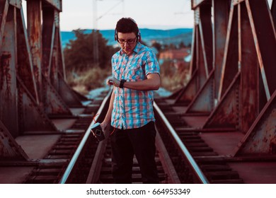 Young man with coffee on rail bridge listening music.