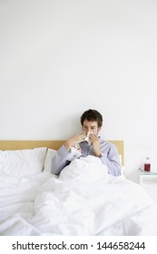 Young man with cold blowing nose in bed