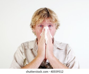 Young man with a cold or flu sneezing - isolated.