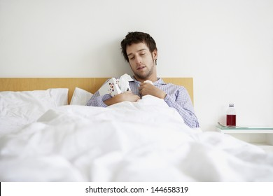 Young man with cold holding box of tissues in bed