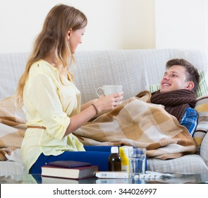 Young man with cold lying on couch, girlfriend taking care