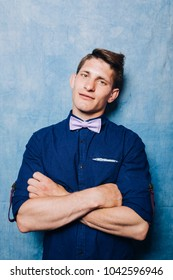 young man in a colored shirt and bow tie. problem skin of a teenager: spots from a burn. emotional portrait of a student. business style attire: pants and wrapped sleeves sweatshirts