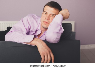 young man in a colored shirt lying on the sofa. emotional portrait. short hair and clean skin. Wallpaper for desktop