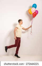 Young man with colorful balloons standing on grey background.