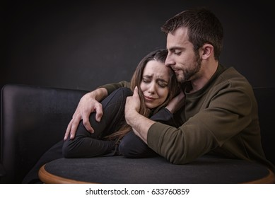 Young man comforting his girlfriend, hugging her and keeping her from harm, woman is crying and feeling sad