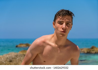 young man coming out of the sea after swimming
