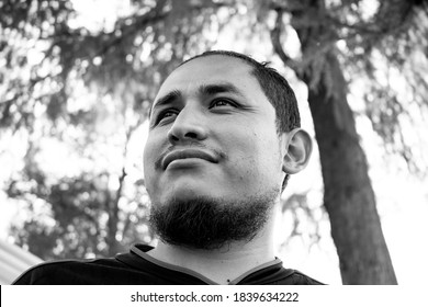 Young man with the common characteristics of a Mexican or Latino looking satisfied towards the horizon. Mexico City, march 2018.
