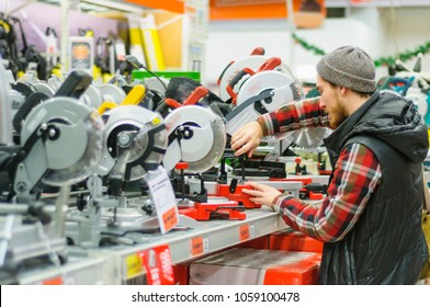A young man compares miter saw in the hardware store