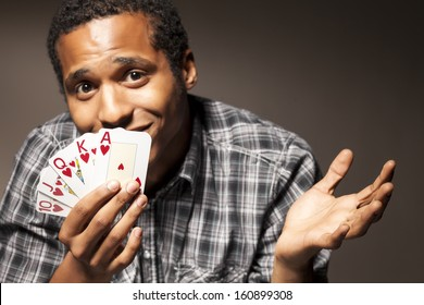 young man with compassion holds the winning combination of poker cards