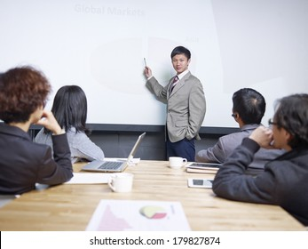 young man conducting presentation in front of  small group of people.