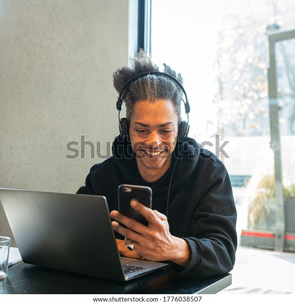 young man is connected with his laptop and smartphone, young student is creating new ides and project on the web, lifestyle concept of blogger and influencer, smart working