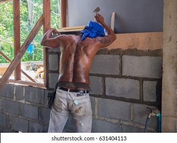 Young man is construction worker  is working hard Building a wall to build a house - 30 Apr 2017, Chonburi Province, Thailand