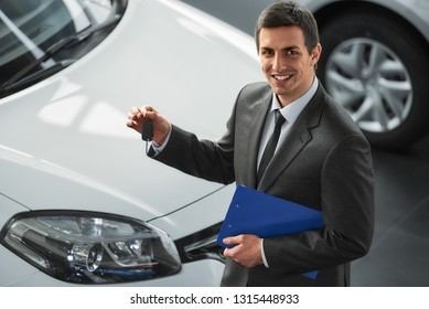 Young man consultant in showroom is standing near car. Top view.