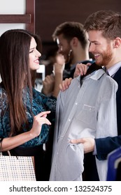 Young man consults with girlfriend while selecting a stylish shirt