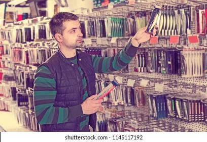 Young man consumer choosing ocean fishing lures in  fishing shop