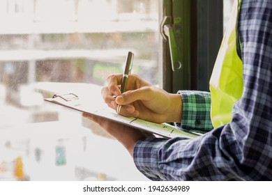 Young man contractor, engineering or employee holding, clipboard, looking at paperwork on the inspecting the reconstructed construction and renovation after to check defect of apartment,home at site.