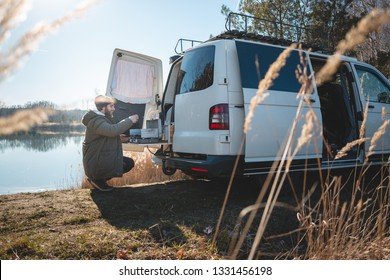 Young man with a converted van at a lake in nature
