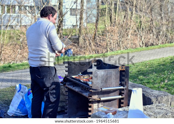 Young man cooking barbeque on grill outdoors