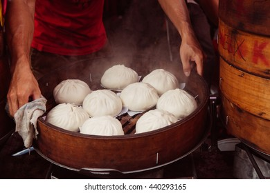 Young man cooking chinese traditional steamed buns at the street food stall in Chinatown, Kuala Lumpur, Malaysia.
