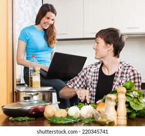 Young man cooking food while girlfriend looking at laptop  in  kitchen