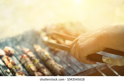 Young man cooking meat on barbecue - Chef putting some meat skewers on grill in garden outdoor - Summertime, food and outside dinner concept - Focus on top hand