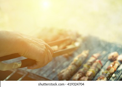Young man cooking meat on barbecue - Chef putting some meat skewers on grill in park outdoor - Concept of eating outdoor during summer time - Vintage retro filter with sun halo flare