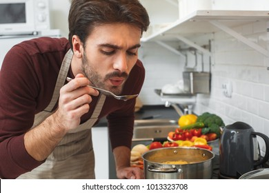 Young man cooking romantic dinner at home taste soup