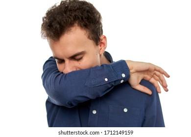 Jeune homme toussant dans son coude