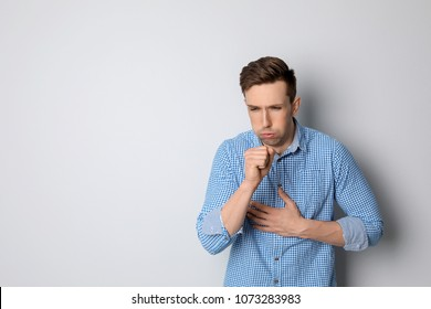 Young man coughing on light background