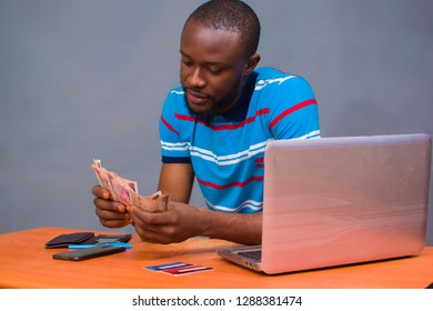 Young man counting his monmey in his office with his laptop on his table