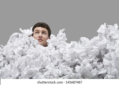 Young man covered in crumpled papers looking up against gray background