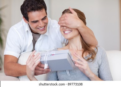 Young man covering the eyes of his girlfriend while giving her a present
