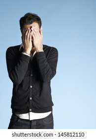Young man covering face with hands isolated on blue background