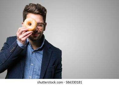 young man covering his eye with a donut