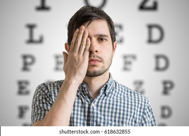 Young man is covering his face with hand and checking his vision. Chart for eye sight testing in background.