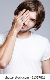 young man covers face with hand, studio shot